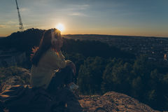 Young pretty woman listing music on the top of the hill. On sunset Royalty Free Stock Photo