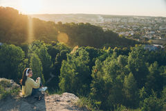 Young pretty woman listing music on the top of the hill. On sunset Royalty Free Stock Image
