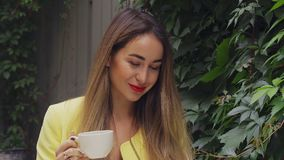 A young pretty woman with long brown hair and a yellow coat is sitting in a street cafe, smiling and drinking coffee. Cloudy summe. R evening. Close-up stock video footage