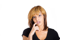 Young pretty woman looking at the camera, biting her nail in disbelief Stock Photo