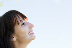 Young pretty woman looking at the sunny sky and smiling. Natural happiness and fun Royalty Free Stock Image