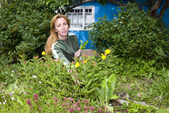 Young pretty woman looks after behind plants in th Stock Photos