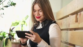 Young pretty woman looks at photos on social networks on her mobile phone stock footage