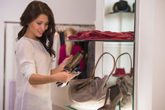 Young pretty woman at luxury boutique choosing accessories Royalty Free Stock Image