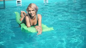 Young pretty woman lying on air mattress in the swimming pool stock photos