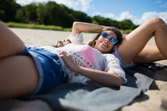 Young pretty woman lying on beach with friend smiling Royalty Free Stock Image