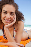 Young pretty woman lying on the beach with her hand on her cheek Stock Photography