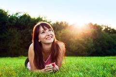 Young pretty woman lying on the grass and smiling at summer sunset Stock Photo