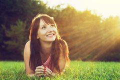 Young pretty woman lying on the grass and smiling at summer sunset royalty free stock photography
