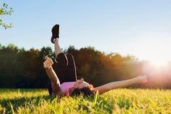 Young pretty woman lying on the grass at summer sunset stock photography