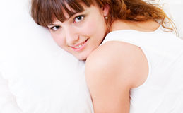 Young pretty woman lying on pillow. Young pretty woman in white nightie lying on pillow Stock Images