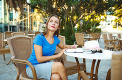 Young pretty woman makes notes in a notebook in a cafe Royalty Free Stock Image