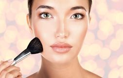 Young pretty woman with a makeup brush royalty free stock photos