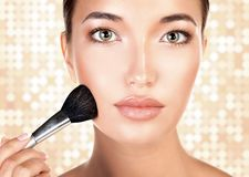 Young pretty woman with a makeup brush royalty free stock images