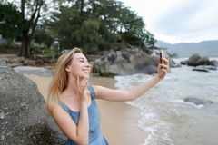 Young pretty woman making selfie by smartphone on empty beach near sea. stock photo