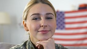 Young pretty woman in military uniform looking camera, america flag background. Stock footage stock footage