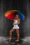 Young woman with multi-coloured umbrella. Young pretty woman with multi-coloured umbrella under rain on a black background stock photography