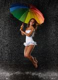 Young woman with multi-coloured umbrella. Young pretty woman with multi-coloured umbrella under rain on a black background stock image