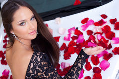 Young pretty woman with a New car in red rose peta Royalty Free Stock Photos