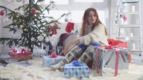 Young pretty woman opens a gift box by a christmas tree. slow motion. 3840x2160 stock video footage