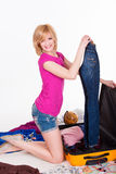 Young pretty woman packing her suitcase before Royalty Free Stock Image