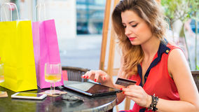 Young pretty woman with pad holding credit card.She is siting in cafe. Close-up Royalty Free Stock Photos