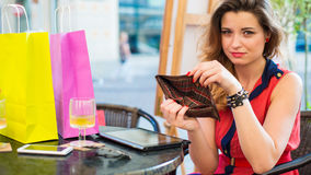 Young pretty woman with pad holding empty wallet. She is siting in cafe. Stock Photo
