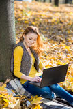 Young pretty woman in the park with laptop Royalty Free Stock Image