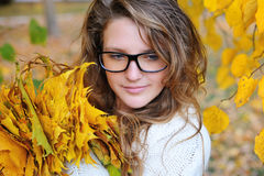 Young pretty woman in park makes a wreath of leaves. Young pretty woman in the autumn park makes a wreath of leaves stock image