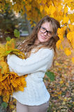 Young pretty woman in park makes a wreath of leaves. Young pretty woman in the autumn park makes a wreath of leaves stock photo