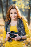 Young pretty woman in the park with photocamera Stock Images