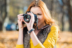 Young pretty woman in the park with photocamera Royalty Free Stock Photo