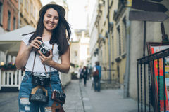 Young pretty woman photographer walk by old city street with retro camera Royalty Free Stock Photography