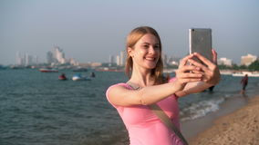Young pretty woman in pink t-shirt taking selfie on beach sea sunset boats cityscape at background. Young pretty woman in pink t-shirt taking selfie on her stock footage