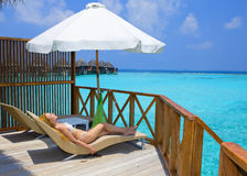 Young pretty woman on platform at villa on water, Royalty Free Stock Photo