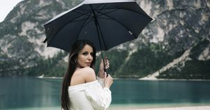 Young pretty woman playing with her umbrella on the beach of a amazing lake and looking to the camera. 4k stock video