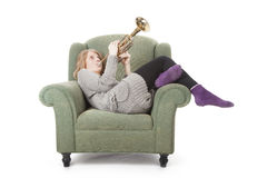 Young pretty woman playing the trumpet sitting on armchair Royalty Free Stock Photo