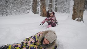 Young pretty woman plays with her baby in snow drifts. They are dressed warmly, so do not afraid of cold. A woman very stock video footage