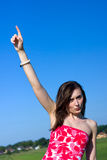 Young pretty woman points her finger at the sky Stock Photos