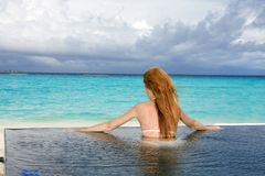 Young pretty woman in the pool and ocean in the ba Royalty Free Stock Photo