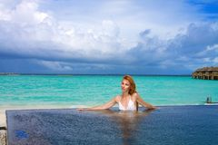 Young pretty woman in the pool and ocean in the ba Royalty Free Stock Images