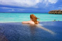 Young pretty woman in the pool and ocean in the ba Stock Images