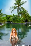 Young pretty woman in pool in tropical garden Stock Image