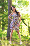 Young pretty woman poses showing dress summer outdoors in sunset Stock Image