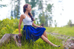 Young pretty woman poses showing dress summer outdoors in sunset Royalty Free Stock Photography