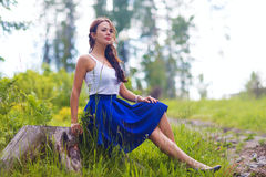 Young pretty woman poses showing dress summer outdoors in sunset Stock Photography