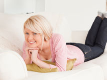 Young pretty woman posing while lying on a sofa Royalty Free Stock Photography
