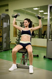 Young pretty woman pumping up muscles with dumbbells Royalty Free Stock Photo