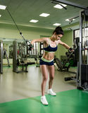 Young pretty woman pumping up muscles with training apparatus Royalty Free Stock Image