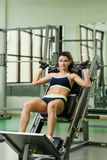Young pretty woman pumping up muscles with training apparatus Stock Image
